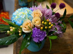 A lovely purple, blue and yellow arrangement in a glass vase